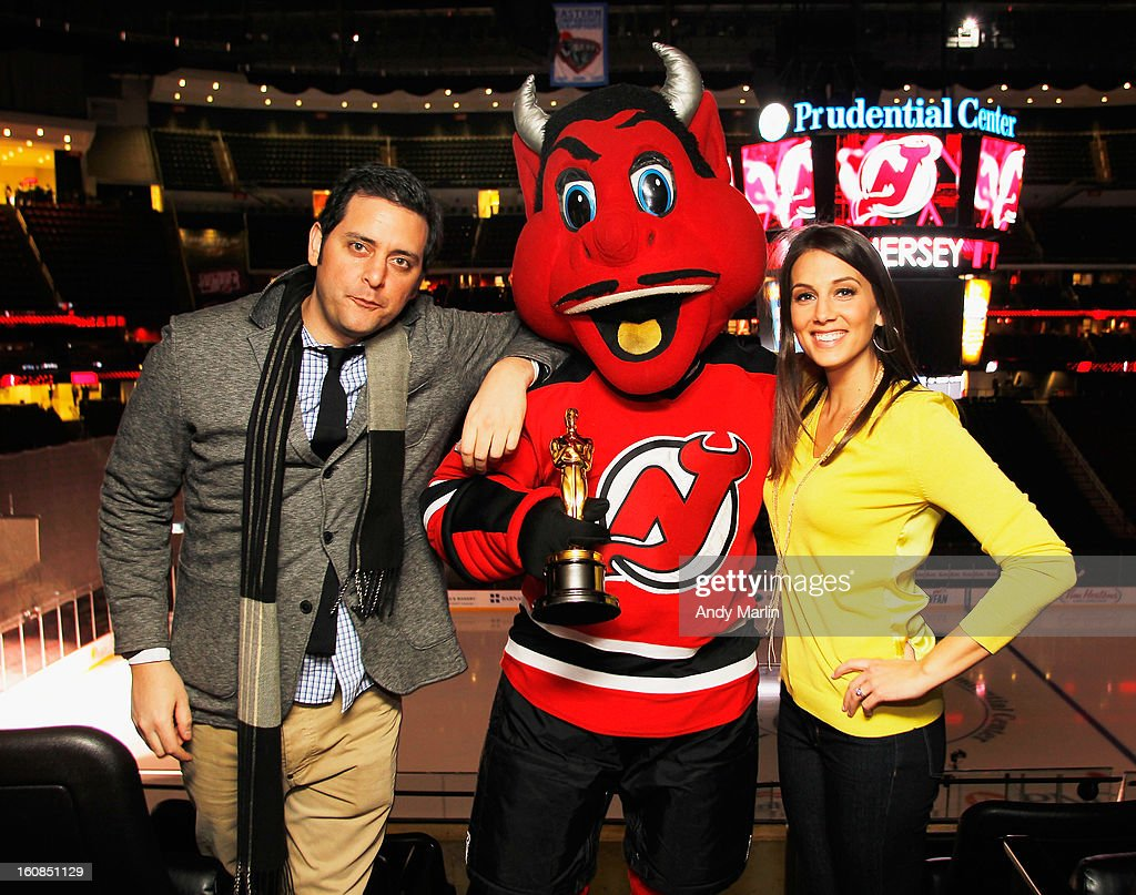 Standup comedian, actor, writer Ben Gleib (L) and standup comedian Angie Greenup pose with mascot NJ Devil with the 'Oscar' prior to the game between the New York Rangers and the New Jersey Devils at the Prudential Center on February 5, 2013 in Newark, New Jersey.