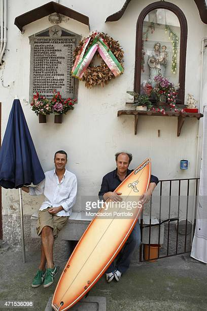'Standup comedians Ale e Franz Alessandro Besentini and Francesco Villa respectively sitting on a bench in the courtyard in Naviglio Martesana via...