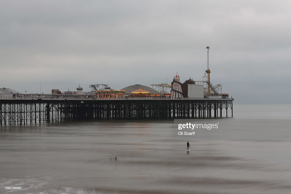A stand-up paddle surfer waits for suitable waves in front of Brighton Pier on January 9, 2013 in Brighton, England.