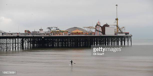 A standup paddle surfer waits for suitable waves in front of Brighton Pier on January 9 2013 in Brighton England