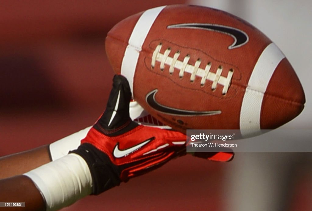 Stanford University football player wearing NIke football gloves catching a Nike football during pregame warm ups before an NCAA football game...