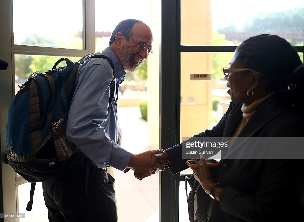Stanford visiting professor Alvin Roth (L) shakes hands with a woman during a press conference announcing his Nobel Prize in economics on October 15, 2012 in Stanford, California. Americans Alvin Roth and Lloyd Shapley were awarded the prize for their work on market design and matching theory.