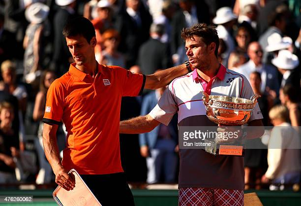 Stanislas Wawrinka of Switzerland holds the Coupe de Mousquetaires as he consoles runner up Novak Djokovic of Serbia after their Men's Singles Final...