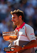Stanislas Wawrinka of Switzerland holds the Coupe de Mousquetaires after victory in the Men's Singles Final against Novak Djokovic of Serbia on day...