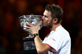 Stanislas Wawrinka of Switzerland kisses the Norman Brookes Challenge Cup after winning his men's final match against Rafael Nadal of Spain during...