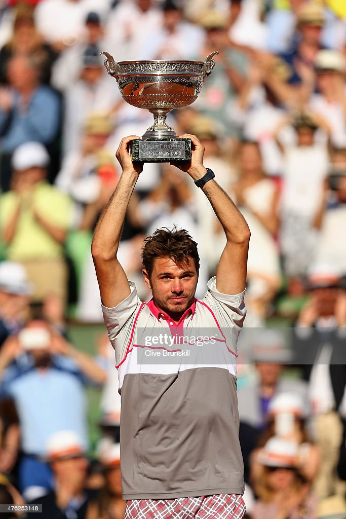 Stanislas Wawrinka of Switzerland lifts the Coupe de Mousquetaires after victory in the Men's Singles Final against Novak Djokovic of Serbia on day...