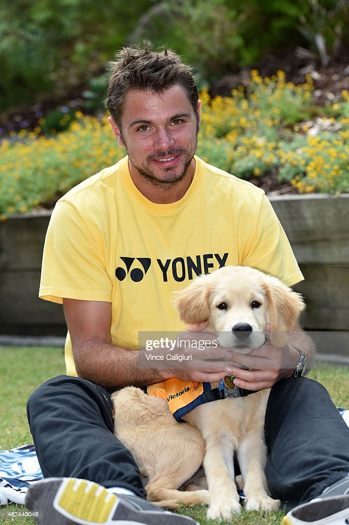 Stanislas Wawrinka of Switzerland meets a guide dog puppy during the 2015 Australian Open at Melbourne Park on January 29, 2015 in Melbourne, Australia.