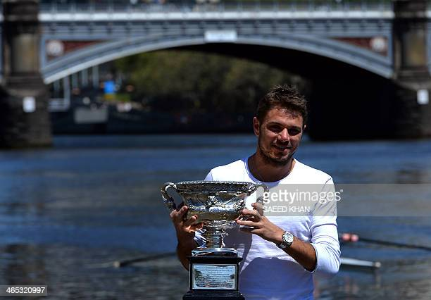 Stanislas Wawrinka of Switzerland poses with the 2014 Australian Open winner's trophy on the bank of the Yarra river in Melbourne on January 27...