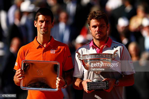 Stanislas Wawrinka of Switzerland poses with the Coupe de Mousquetaires and runner up Novak Djokovic of Serbia after their Men's Singles Final on day...