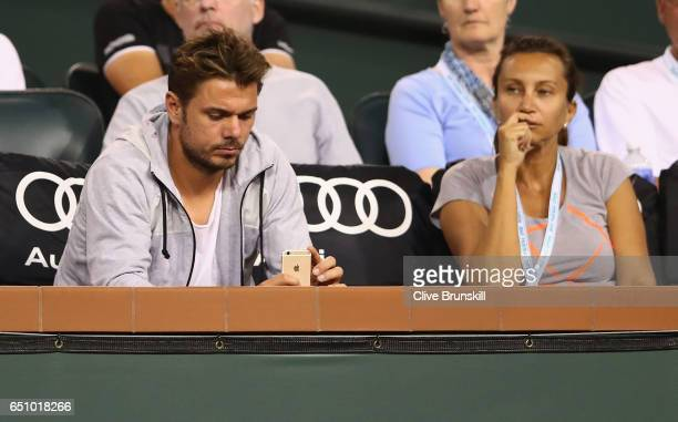Stanislas Wawrinka of Switzerland takes a photograph of Donna Vekic of Croatia as he sits with her coach Iva Majoli to watch her straight sets...