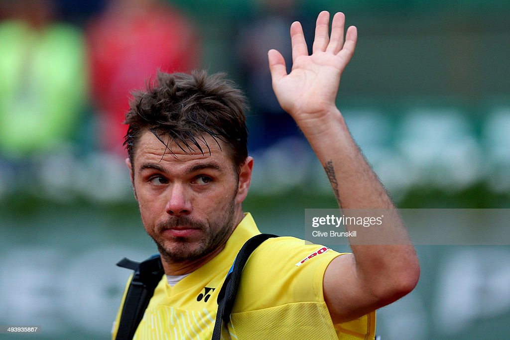 Stanislas Wawrinka of Switzerland waves to the crowd as he leaves court following his defeat in his men's singles match against Guillermo Garcia-Lopez of Spain on day two of the French Open at Roland Garros on May 26, 2014 in Paris, France.
