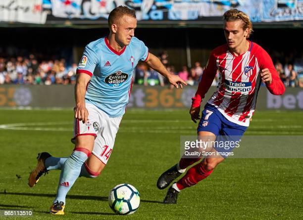 Stanislav Lobotka of Celta de Vigo is challenged by Antoine Griezmann of Atletico de Madrid during the La Liga match between Celta de Vigo and...