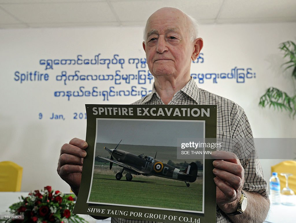 Stanley Coombe, a 91-year-old former British soldier who is one of eight people who said they have seen the buried British Spitfires, poses with a photo of a plane during a press conference at a hotel in Yangon on January 9, 2013. A British-led excavation team hunting for dozens of rare Spitfires in Myanmar said during the press conference on January 9 they were confident of recovering the World War II-era planes after finding a crate buried in the ground. Britain is thought to have buried brand new planes in 1945 as they were surplus by the time they arrived by sea. AFP PHOTO / Soe Than WIN