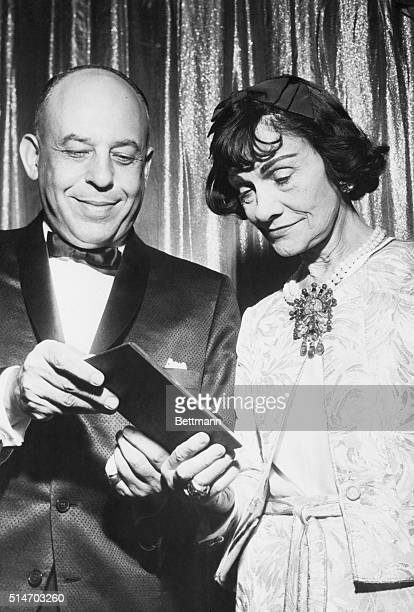 Stanley Marcus presents the NeimanMarcus fashion award for 1957 to Gabrielle Chanel during the awards banquet in the ballroom of the StatlerHilton in...
