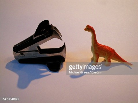 Staple Remover And Dinosaur Toy On White Background