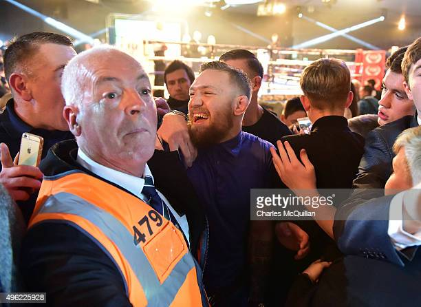 UFC star Conor McGregor is mobbe by fans after being interviewed ringside as he attended The Second Coming boxing bill at the National Stadium on...