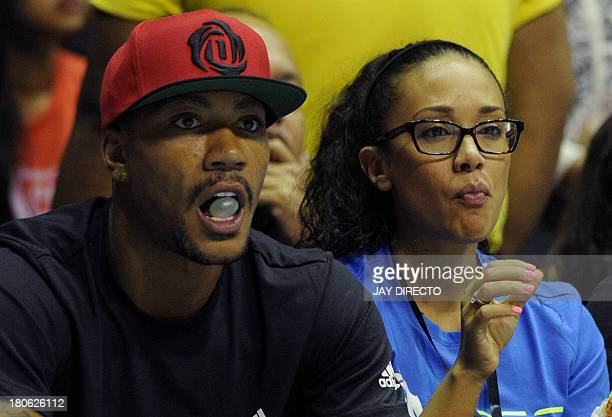 NBA star Derrick Rose of the Chicago Bulls pops his bubble gum as he watches intercollegiate basketball in Manila with an unidentified woman on...