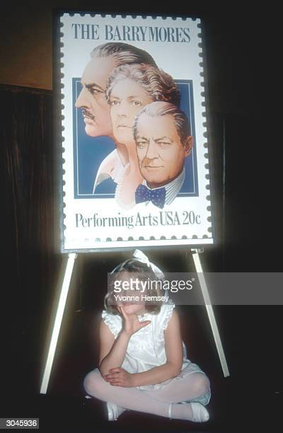 'ET' star Drew Barrymore poses for a photograph with a postage stamp honoring the Barrymore family June 8 1982 in New York City