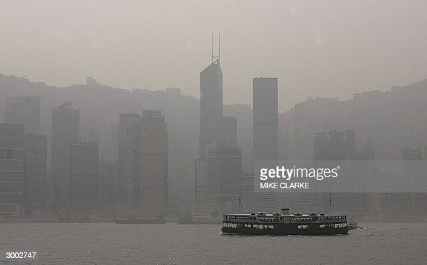Star Ferry boat which plies the harbor between Kowloon and Hong Kong island passes in front of the polluted smogridden skyline of Hong Kong 22...