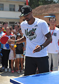 NBA star George Hill plays pingpong as he attends a charity activity with leftbehind children at a school on July 22 2016 in Fuyang Anhui Province of...
