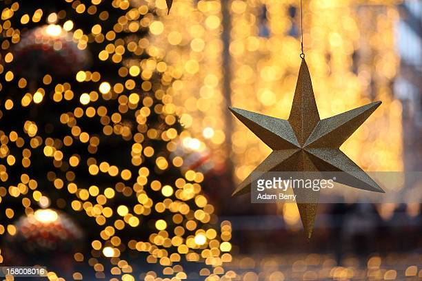 A star hangs near a Christmas tree during Christmas shopping season in a shopping mall on December 8 2012 in Berlin Germany German consumer...