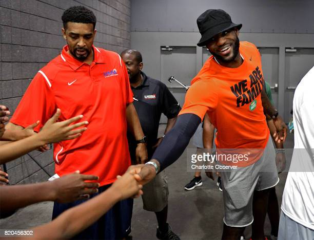 NBA star LeBron James right reaches out to shake hands with fans following his son LeBron Jr's tournament game at the Charlotte Convention Center in...