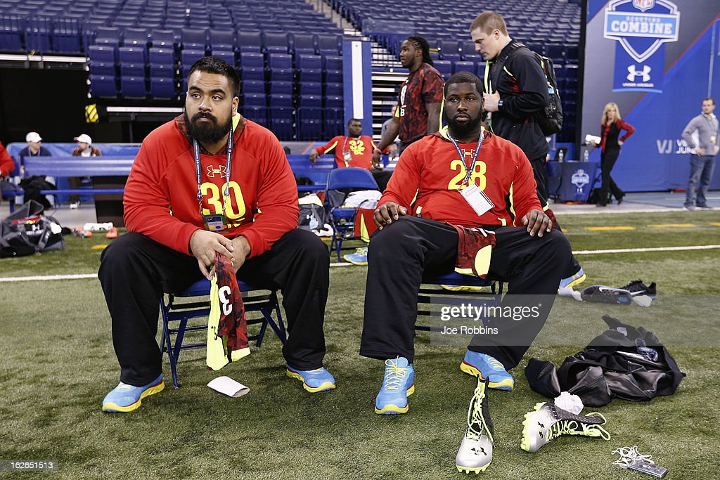 Star Lotulelei (left) of Utah and Kapron Lewis-Moore (right) of Notre Dame watch the workouts during the 2013 NFL Combine at Lucas Oil Stadium on February 25, 2013 in Indianapolis, Indiana.