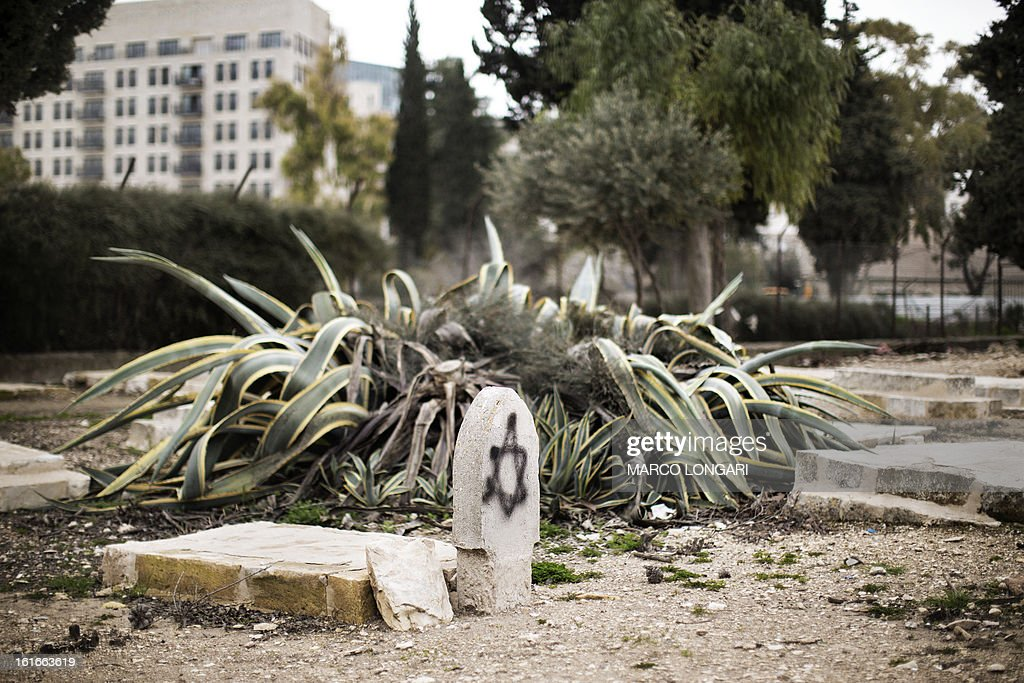 A Star of David is seen spray painted on a gravestone at the Mamun Allah cemetery, an old Muslim cemetery in Jerusalem on February 14, 2013. The price tag attack was an apparent revenge for the evacuation of the outpost of Maale Rehavam, destroyed yesterday by Israeli forces in the West Bank. AFP PHOTO/MARCO LONGARI