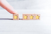 4 Star Rating Formed By Wooden Blocks And Arranged By A Male Finger On White Table