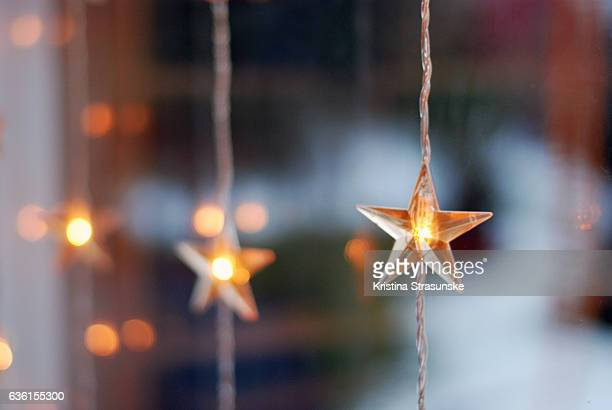 star shaped christmas lights in a window