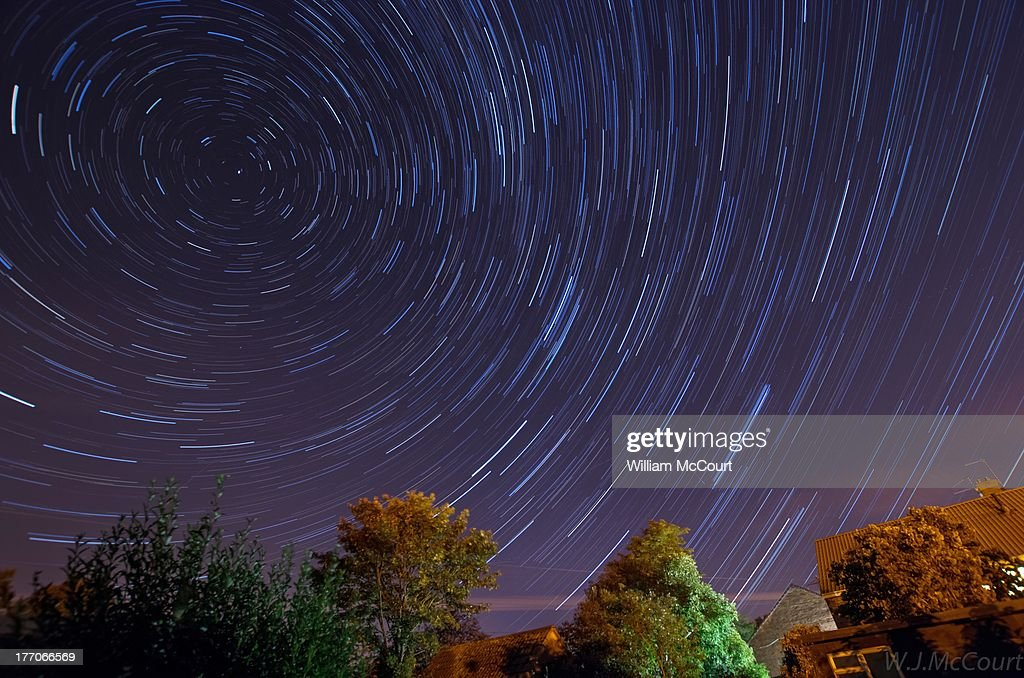 CONTENT] Star trails over a light polluted Sutton Courtenay (a small village in Oxfordshire). A meteor from the Perseid meteor shower is visible.