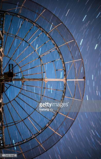 Star trails over a radio telescope antenna