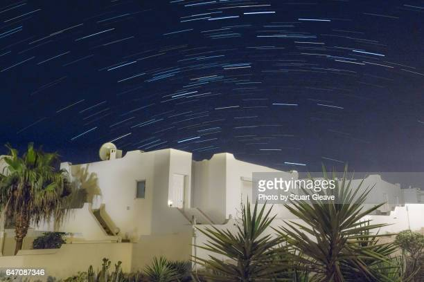 Star trails over Spanish villas and palm trees