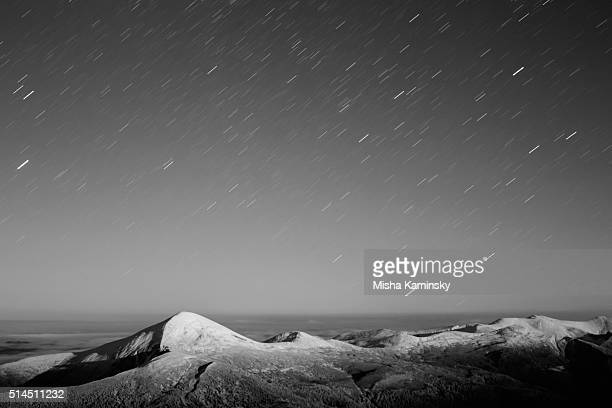 Star trails over the snowy mountain range