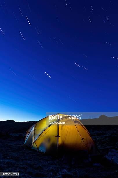 Star trails over yellow mountain tent