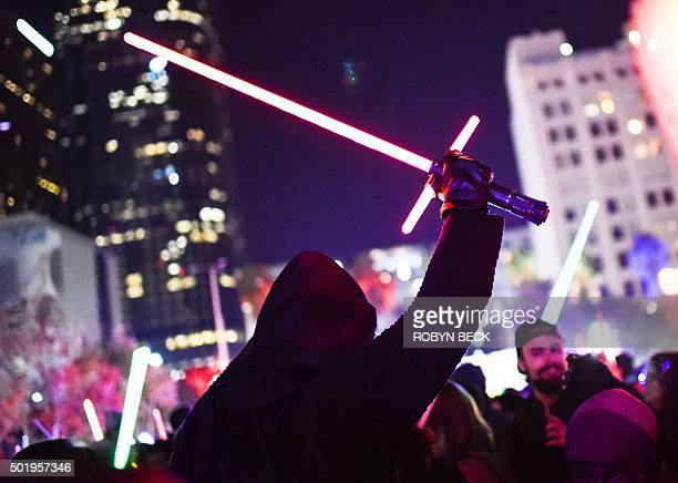 A Star Wars fan dressed as Kylo Ren raises his lightsaber during Lightsaber Battle LA in Pershing Square in downtown Los Angeles California on...