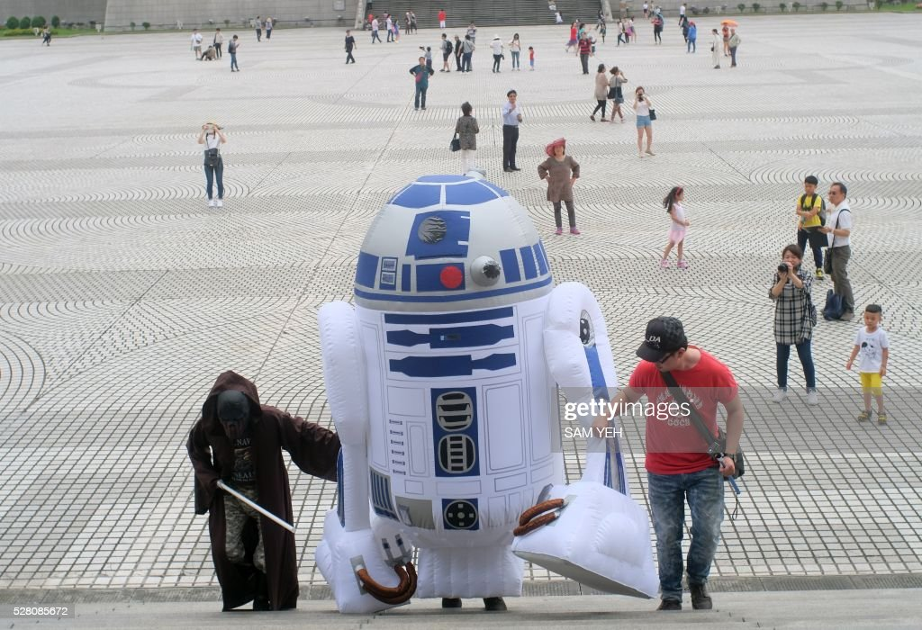 A Star Wars fan, dressed as R2D2 robot, arrives during the annual Star Wars Day in Taipei on May 4, 2016. Some 100 star wars fans dress the different costumes during a cosplay event to mark the annual Star War Day. / AFP / SAM YEH