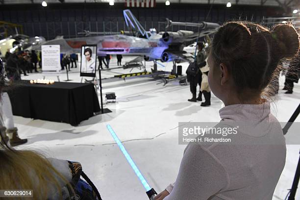 'Star Wars' fan Elizabeth Boettcher holds her lightsaber during a candlelight vigil for actress Carrie Fisher at The Wings Over the Rockies Air and...