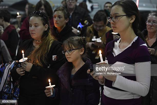 'Star Wars' fan Reyna Palmer middle Kim Terasaki right and other fans of all ages hold up candles and lightsabers during a vigil for actress Carrie...