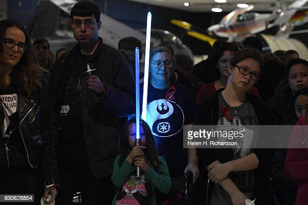 'Star Wars' fans Anne Hatzakis in middle with her daughter Mira hold lightsabers during a candlelight/lightsaber vigil for actress Carrie Fisher at...