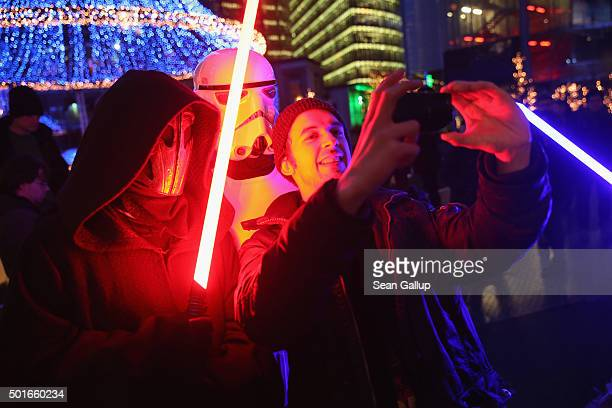 Star Wars fans some armed with light sabers shoot a selfie as they arrive for a midnight plus one minute first regular screening of 'Star Wars The...