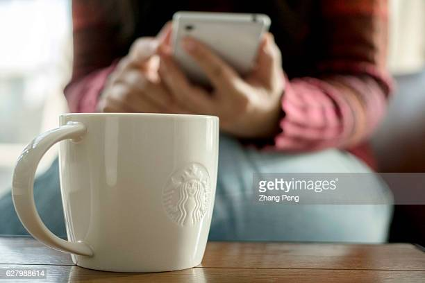 Starbucks coffee cup on table beside which a customer is reading on mobile phone At the end of November a Chinese customer posted an open letter...