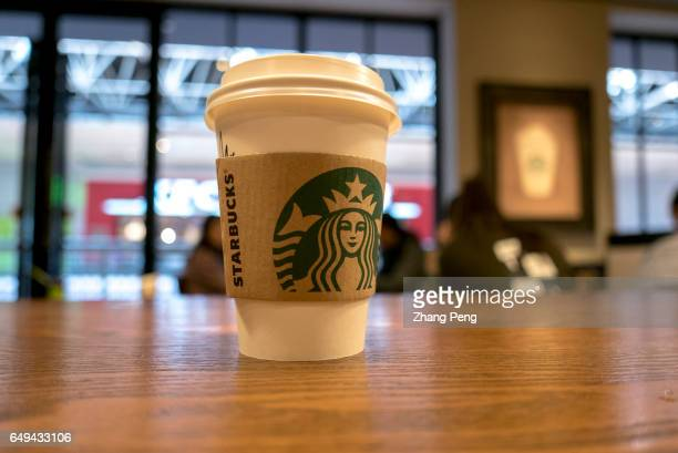 Starbucks coffee cup on table Starbucks is growing fast in China and aims to double its locations there in the next five years to reach 5000 stores...