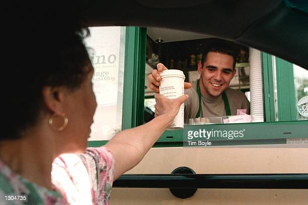 Starbucks Coffee employee Mike Crudele delivers a coffee order to customer Juanita Richardson through a window as she sits in her car at a driveup...