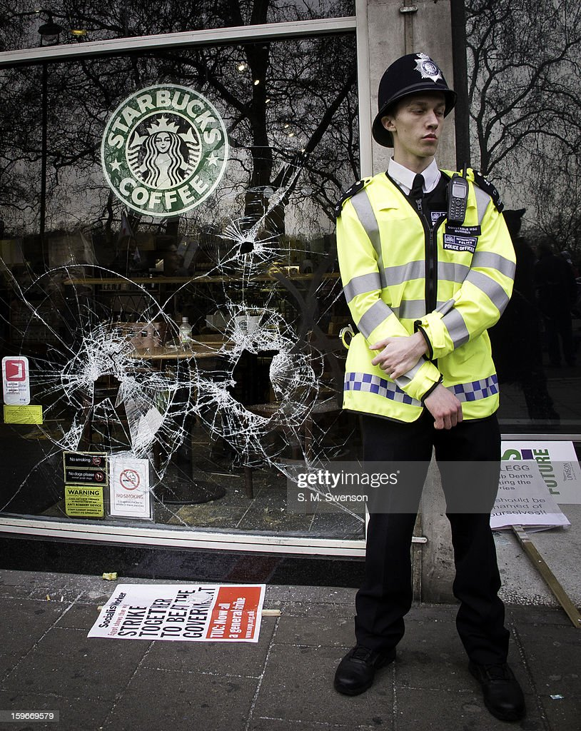 Starbucks coffee shop in Mayfair, Central London is vandalised by anti-globilisation anarchists during a march against government cuts. A window is smashed and a policeman stands on guard in front of the shop to prevent further vandalism. Political placards are strewn about. Taken on the afternoon of March 26, 2011.