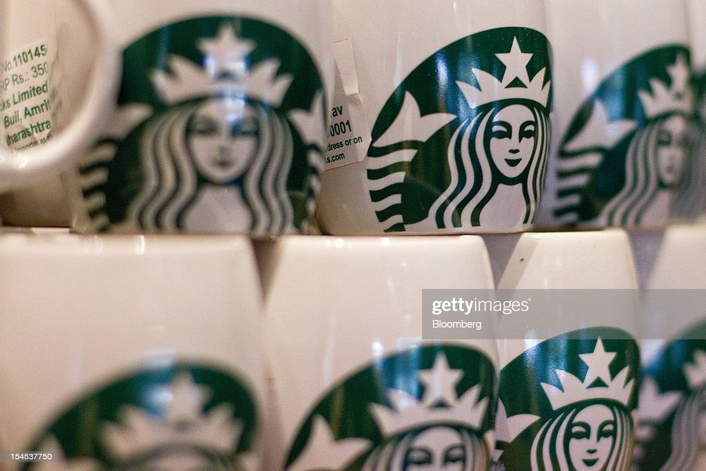 Starbucks Corp.-labeled mugs are stacked inside the company's first India outlet in Mumbai, India, on Friday, Oct. 19, 2012. Starbucks, which opened its first store in India today, will maintain its partnership with Tata Global Beverages Ltd. and plans to take some of that company's products to new markets, Starbucks' Chief Executive Officer Howard Schultz said. Photographer: Dhiraj Singh/Bloomberg via Getty Images