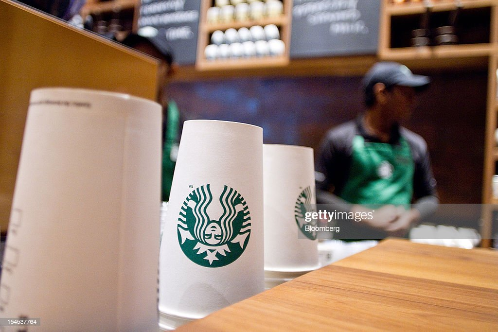 Starbucks Corp.-labeled paper cups are stacked at the counter at the company's first India outlet in Mumbai, India, on Friday, Oct. 19, 2012. Starbucks, which opened its first store in India today, will maintain its partnership with Tata Global Beverages Ltd. and plans to take some of that company's products to new markets, Starbucks' Chief Executive Officer Howard Schultz said. Photographer: Dhiraj Singh/Bloomberg via Getty Images