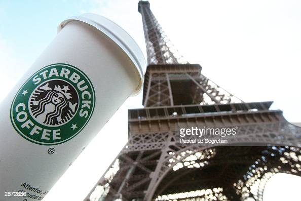 Starbucks cup is seen in front of the Eiffel tower as the new Starbucks store opened for the public the first ever in France January 16 2004 in Paris...