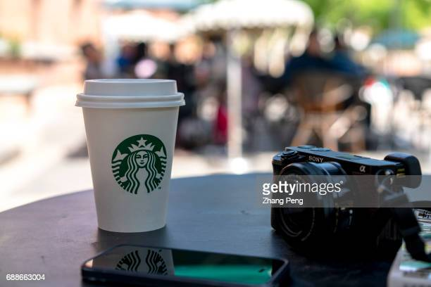Starbucks cup on a roadside table According to the report of the second quarter in 2017 the revenue of Starbucks was $53 billion and the sales growth...