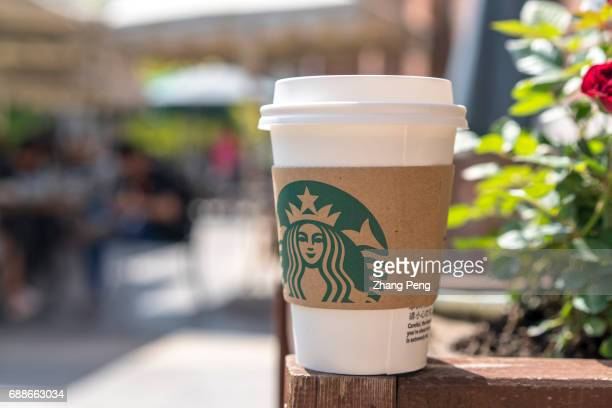 Starbucks cup on wooden railing arranged for photography According to the report of the second quarter in 2017 the revenue of Starbucks was $53...